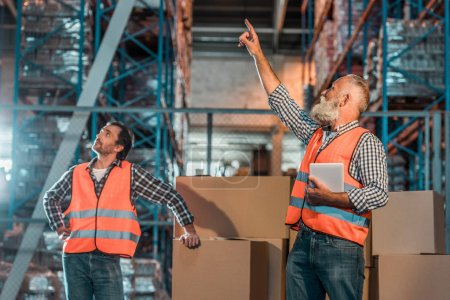 Photo for Warehouse workers in vests holding digital tablet and pointing up with finger - Royalty Free Image