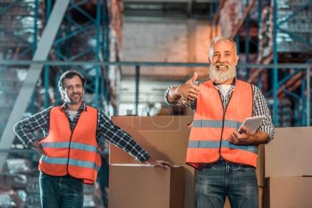 Photo for Cheerful warehouse workers with digital tablet smiling at camera and showing thumb up - Royalty Free Image