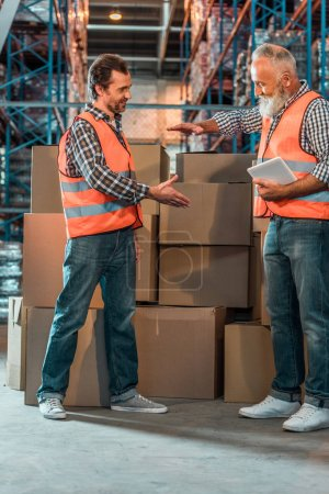 Photo for Smiling warehouse workers in vests shaking hands while holding digital tablet - Royalty Free Image