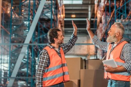 Photo for Side view of smiling warehouse workers giving high five while working with digital tablet - Royalty Free Image