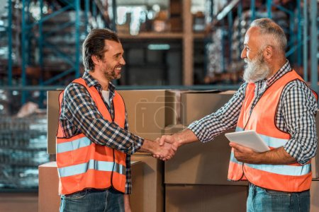 Photo for Side view of smiling warehouse workers shaking hands while holding digital tablet - Royalty Free Image