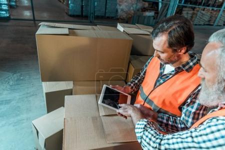 Photo pour Vue d'angle élevé de deux travailleurs de sexe masculin à l'aide de tablette numérique en entrepôt - image libre de droit