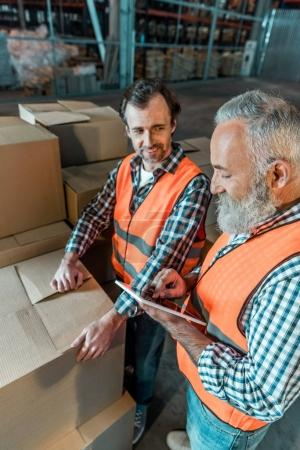 Photo for Smiling warehouse workers with digital tablet working together in storehouse - Royalty Free Image