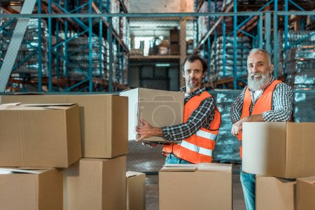 Photo for Two male colleagues in vests working with boxes and smiling at camera in warehouse - Royalty Free Image