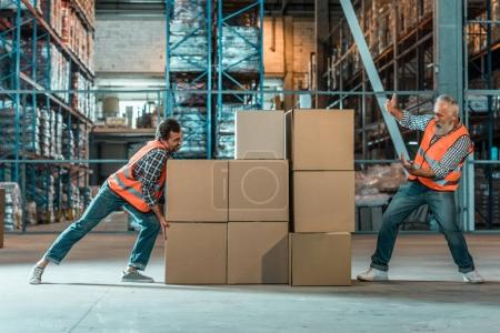 Photo for Warehouse worker moving boxes while male colleague gesturing - Royalty Free Image