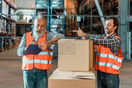 Foto de Barbudo a trabajador maduro escribir en el Portapapeles mientras sonriente colega señalando con el dedo - Imagen libre de derechos