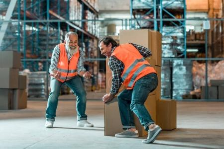 Photo for Smiling bearded worker looking at colleague moving boxes in warehouse - Royalty Free Image