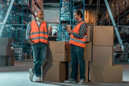 Photo for Two male warehouse workers in vests drinking coffee in storehouse - Royalty Free Image