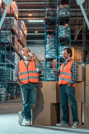 Photo for Middle aged warehouse workers drinking coffee while standing near boxes - Royalty Free Image