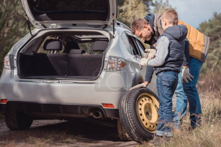 Father and son changing car wheel