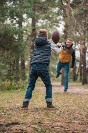 Photo for Back view of little boy throwing ball to father in forest - Royalty Free Image