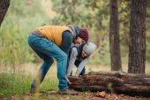father and son moving log in forest