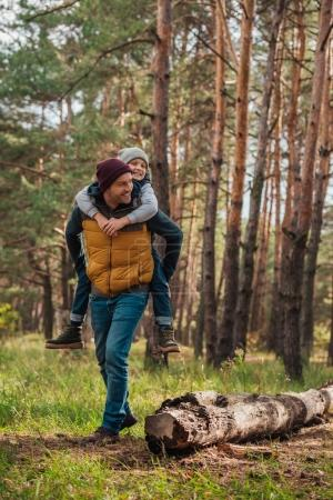 Photo for Father piggybacking happy little son in autumn forest - Royalty Free Image