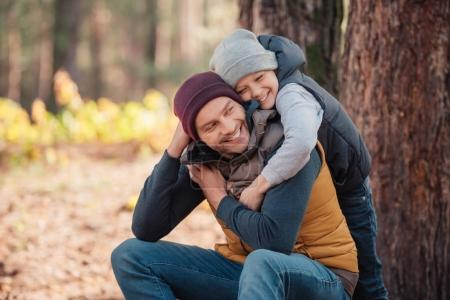 father and son hugging in forest
