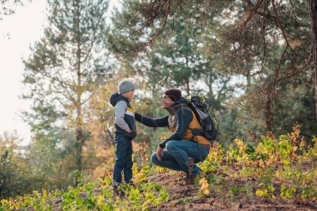 Photo for Father and son looking at each other while hiking together - Royalty Free Image