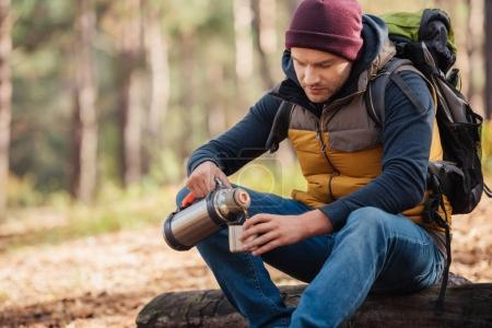 man drinking tea in forest