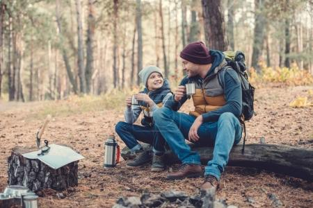 father and son drinking tea in forest