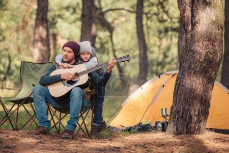 Photo pour Mignon petit garçon câlin père jouer de la guitare dans la forêt - image libre de droit