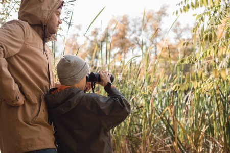 father and son with binoculars