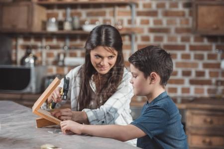 Photo pour Petit garçon et sa belle mère à l'aide de marteau pour construire un nichoir en bois - image libre de droit