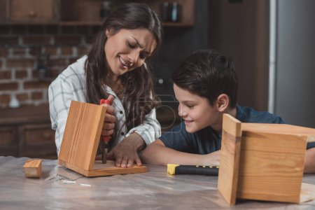 Mother and son building birdhouse