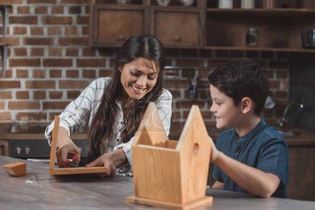 Foto de Pequeño hijo y su hermosa madre bordando un birdhouse de madera con pinzas - Imagen libre de derechos