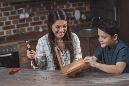 Photo pour Petit fils et son sourire mère artisanat un nichoir en bois dans la cuisine à la maison - image libre de droit