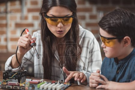 Photo for Little son and his beautiful mother working with soldering iron on electronics school project - Royalty Free Image