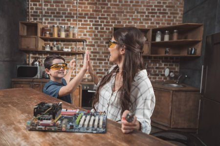 Photo for Little son and his beautiful mother high-fiving while working on a computer motherboard at home - Royalty Free Image