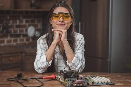Photo for Young woman in protective glasses sitting at table with motherboard on it - Royalty Free Image