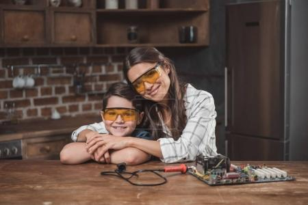 Photo for Little son and his beautiful mother hugging while sitting at table with computer motherboard on it - Royalty Free Image