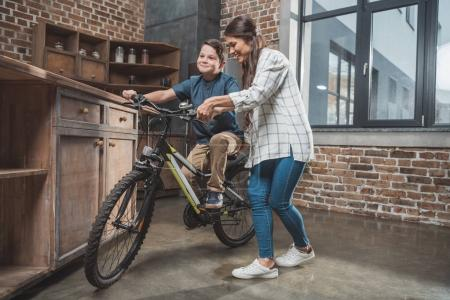 Photo for Young mother teaching her son how to ride a bicycle at home - Royalty Free Image