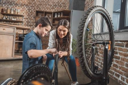 Mother and son fixing bicycle tire