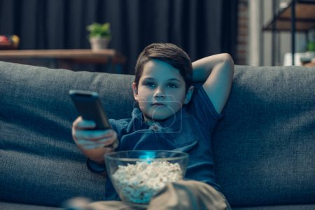 Photo for Little boy sitting on couch with bowl of popcorn and remote control - Royalty Free Image