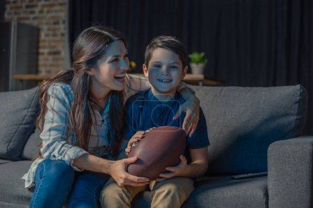 Photo for Little son and his beautiful mother laughing while sitting on couch and watching an american football game - Royalty Free Image
