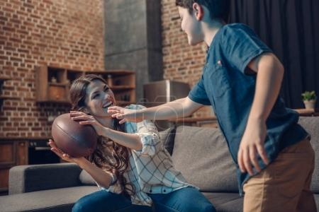 Mother and son playing with rugby ball