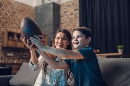 Photo for Little boy and his young mother holding a rugby ball while watching tv on couch in living room - Royalty Free Image