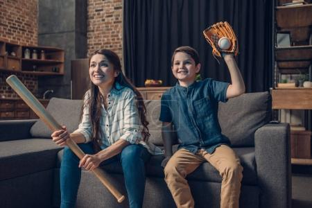 Photo for Little boy and his beautiful mother sitting on couch in living room with baseball bat and mitt, while watching tv - Royalty Free Image
