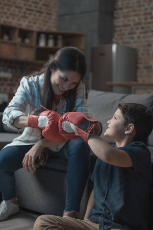 Photo for Little boy and his young mother fistbumping while wearing boxing gloves - Royalty Free Image