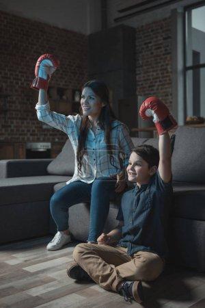 Photo pour Petit garçon et sa mère acclamant tout en portant des gants de boxe et regarder match à la télévision - image libre de droit
