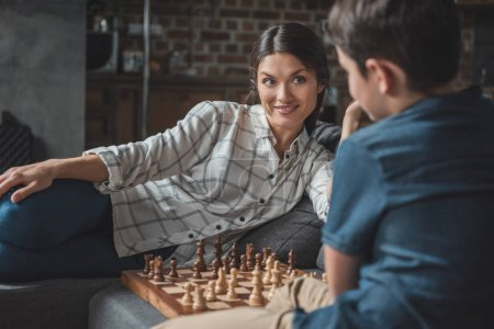 Photo for Young woman looking at her little son while they are playing chess - Royalty Free Image
