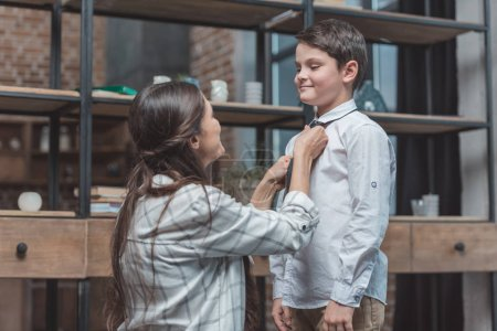 Mother tying necktie on son