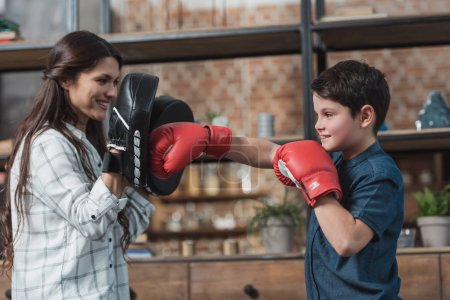 Photo for Little boy in boxing gloves kicking a punching pad held by his mother - Royalty Free Image