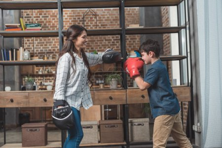 Photo for Little boy in boxing gloves kicking a punching pad held by his mother at home - Royalty Free Image