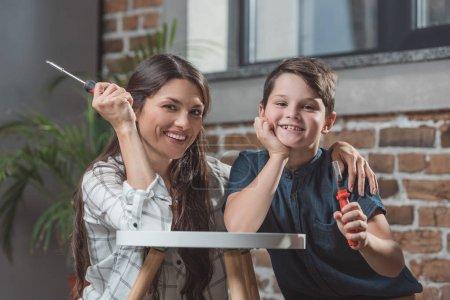 Foto de Niño y su joven madre sentada en el piso en casa, apoyado en una mesa de café y sostener destornilladores - Imagen libre de derechos