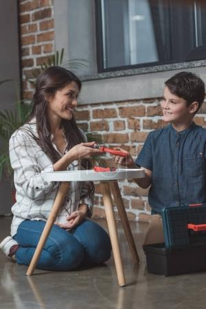 Woman giving pliers to son