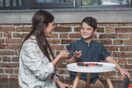 Photo pour Jeune femme distribuant des pinces à son petit fils assis sur le plancher dans le salon - image libre de droit
