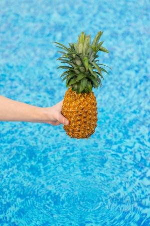 Woman holding pineapple over water