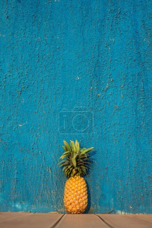 pineapple in front of blue wall