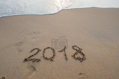 2018 sign on sandy beach